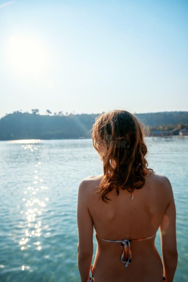 Młoda piękna kobieta w bikini jest trwanie przeciw tłu morze, pojęciu czas wolny i podróży z powrotem, zwrotniki zdjęcie stock