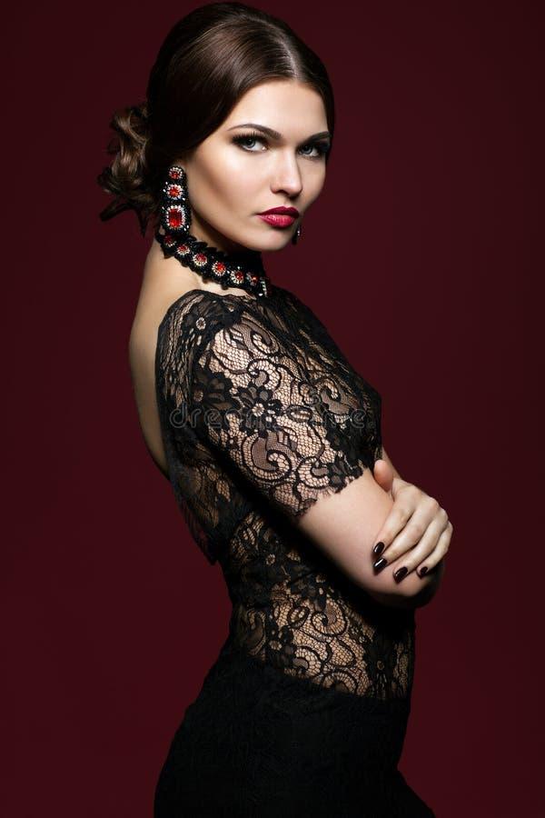 Młoda piękna kobieta w czerni sukni na marsala koloru tle zdjęcia royalty free