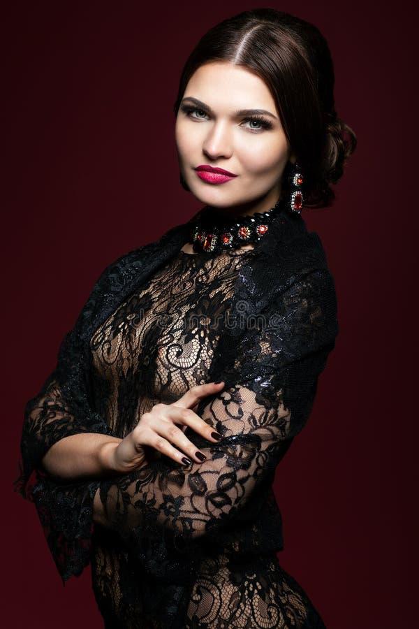 Młoda piękna kobieta w czerni sukni na marsala koloru tle zdjęcie stock