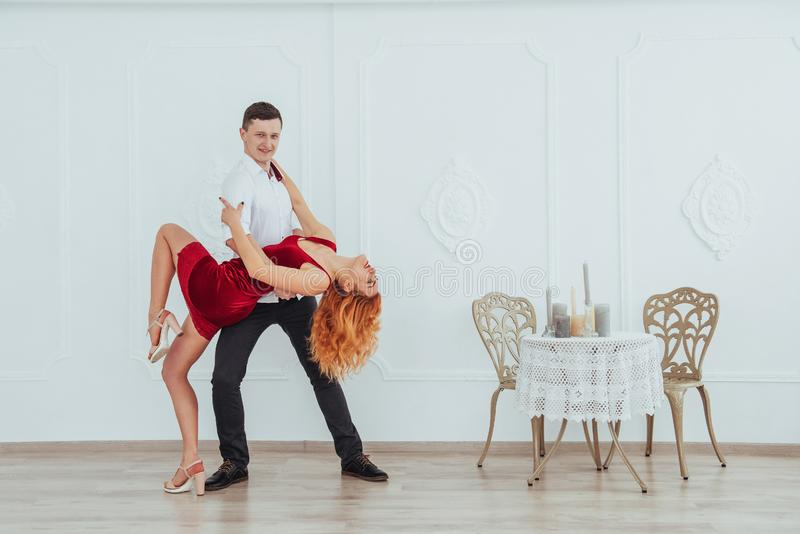 Młoda piękna kobieta w czerwonej sukni i mężczyzna tanu na białym tle, zdjęcie stock