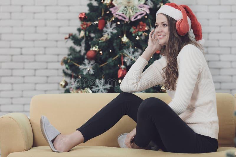 Młoda piękna kobieta w czerwonym kapeluszowym obsiadaniu na kanapie między christm obrazy royalty free