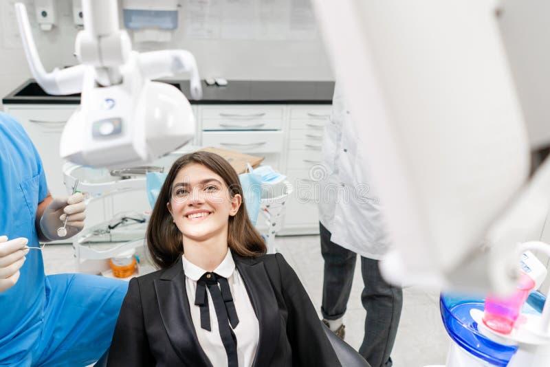 Młoda piękna kobieta w dentysty krześle przy stomatologiczną kliniką Medycyna, zdrowie, stomatology poj?cie dentysta taktuje a zdjęcia stock