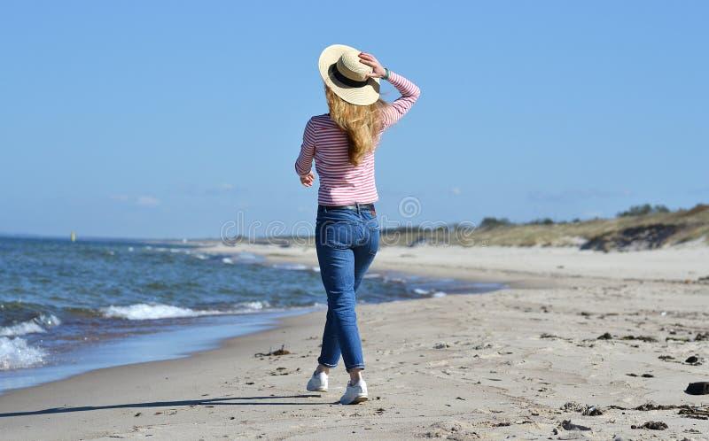 Młoda piękna kobieta w kapeluszu chodzi na morzu zdjęcia stock