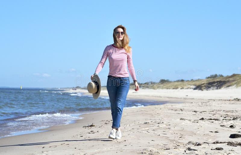 Młoda piękna kobieta w kapeluszu chodzi na morzu obraz stock