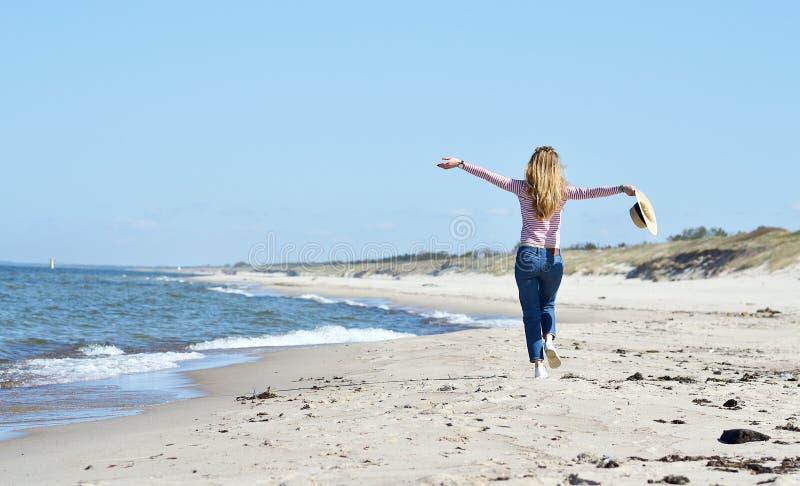 Młoda piękna kobieta w kapeluszu chodzi na morzu obrazy royalty free