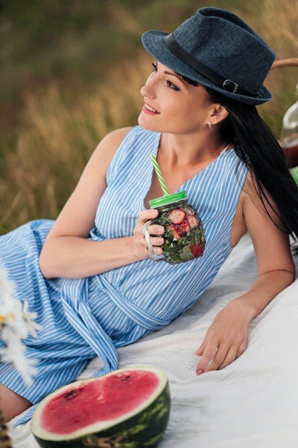 Młoda piękna kobieta w kapeluszu i sukni pije lemoniadę od szklanego słoju, siedzi na szkockiej kracie na zielonej trawie piknik zdjęcie stock
