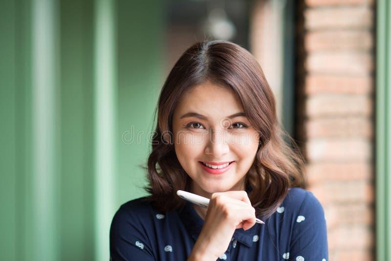 Młoda piękna kobieta w kawiarni blisko okno, główkowania i writing, coś obraz stock