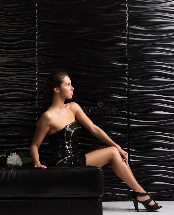 Młoda piękna kobieta w krótkiego czerni smokingowy pozować na leżance fotografia stock