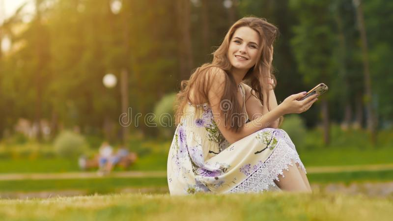 Młoda piękna kobieta w lato sukni z długie włosy obsiadaniem na trawie w zieleń parku i opowiadać na telefonie, ono uśmiecha się zdjęcia royalty free
