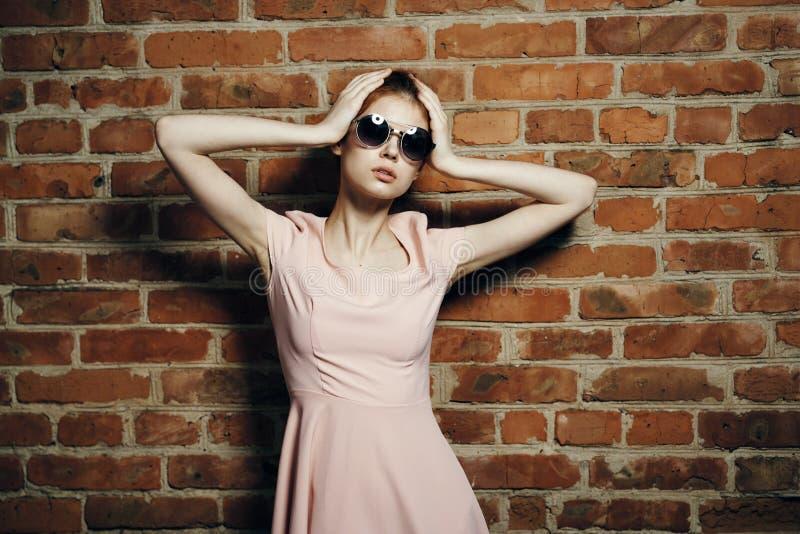 Młoda piękna kobieta w okularów przeciwsłonecznych chwytach dalej głowa blisko kerp ściany zdjęcia stock