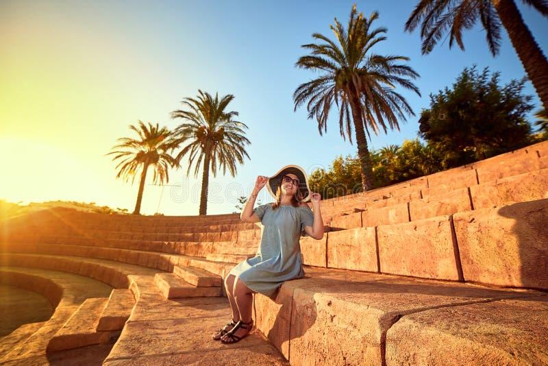 Młoda piękna kobieta w plażowym kapeluszowym obsiadaniu na krokach antyczny amfiteatr przy słonecznym dniem w Bodrum, Turcja waka zdjęcia stock