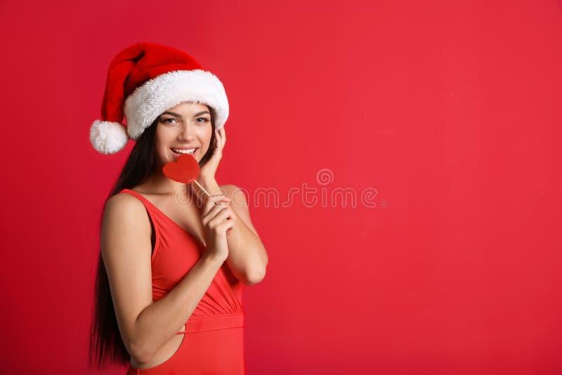 Młoda piękna kobieta w swimsuit i Santa mienia kapeluszowym lizaku na koloru tle świętuje świętowania bożych narodzeń córki kapel fotografia stock
