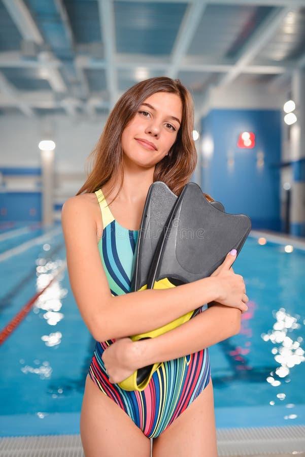 Młoda piękna kobieta w swimsuit z flippers pozuje przy pływackiego basenu terenem zdjęcia stock