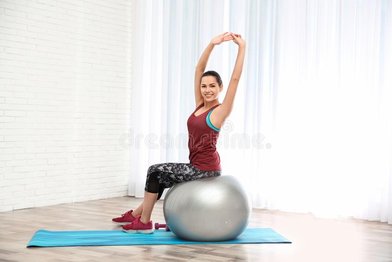 Młoda piękna kobieta z balowym robi ćwiczeniem Trening i sprawność fizyczna obraz stock