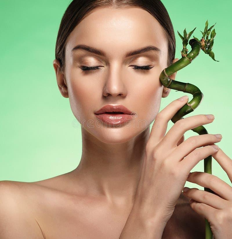 Młoda piękna kobieta z bambusem nad zielonym tłem fotografia royalty free