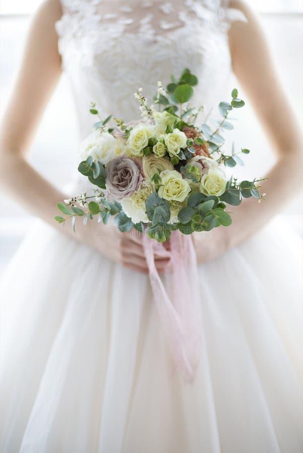 Młoda piękna kobieta z bukietem pozuje w ślubnej sukni Cl zdjęcie stock