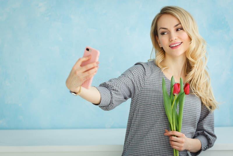 Młoda piękna kobieta z bukietem tulipany ono fotografuje na telefonie obrazy stock
