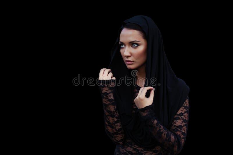Młoda piękna kobieta z czarni włosy w czarnej bluzce przy czarnym tłem i kapiszonie fotografia stock