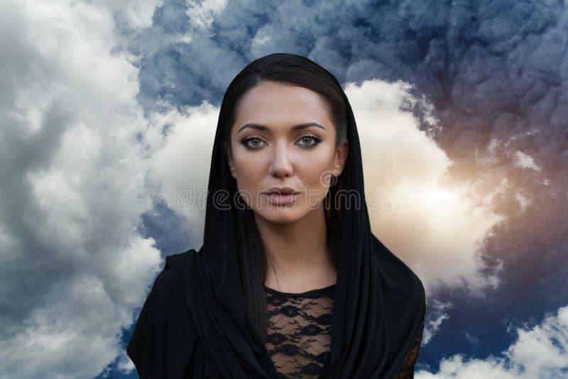 Młoda piękna kobieta z czarni włosy w czarnej sukni z nieba backgtound i obraz royalty free