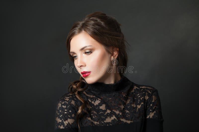 Młoda piękna kobieta z czerwonym wargi makeup włosy na czarnym tle obrazy stock