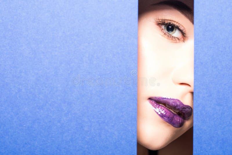 Młoda piękna kobieta z jaskrawym makijażem i fiołkowi warg spojrzenia przez dziury w fiołku tapetujemy Kosmetyki, kosmetyki, pięk obrazy stock