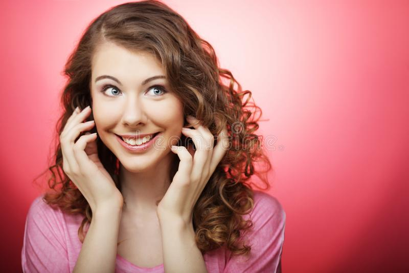 Młoda piękna kobieta z kędzierzawym włosy nad różowym tłem obrazy stock