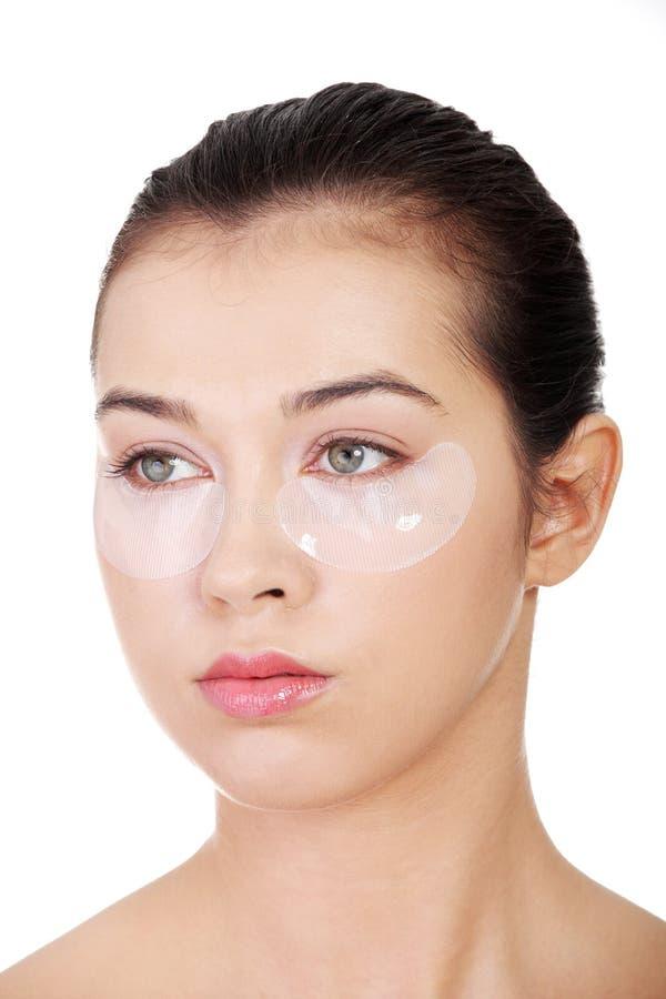 Młoda piękna kobieta z kolagenu oka dźwignięcia maską zdjęcie royalty free