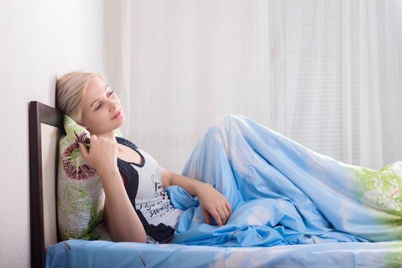Młoda piękna kobieta z krótkiego włosy obsiadaniem na jej łóżku w sypialni w ranku w domu zdjęcie stock