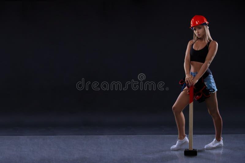 Młoda piękna kobieta z młotem Silna mięśniowa sporty dziewczyna przygotowywająca dla aktywnego ćwiczenia w sporta gym Siły i moty zdjęcia royalty free