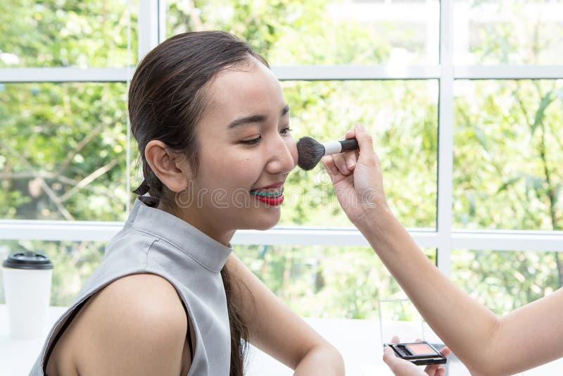 Młoda piękna kobieta z Makeup muśnięciem Przyjaciele robi makijażowi w sklep z kawą obraz royalty free