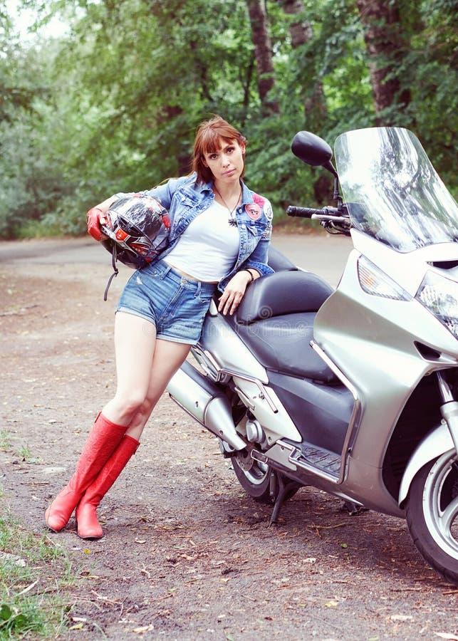 Młoda piękna kobieta z motocyklem outdoors zdjęcia royalty free