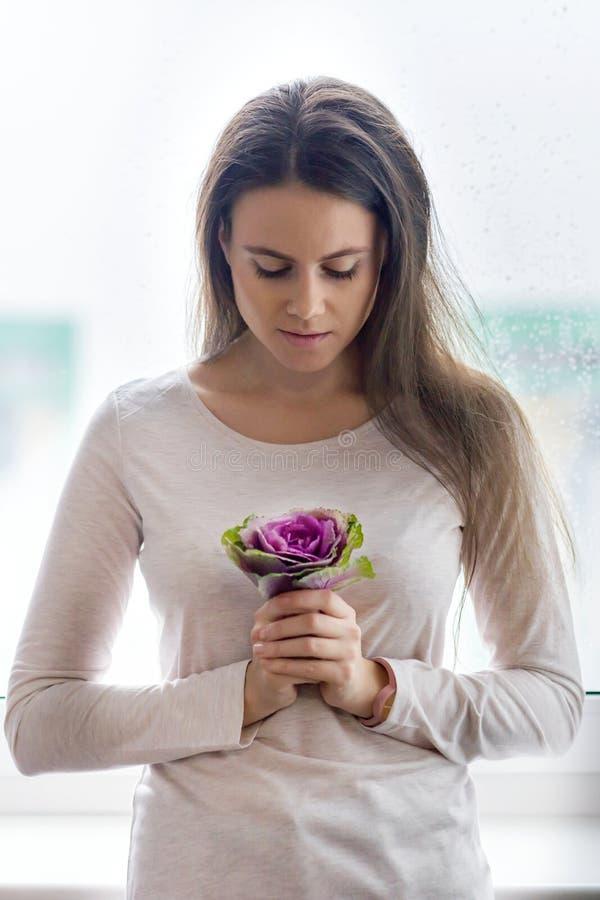Młoda piękna kobieta z naturalnym makeup, długiego i zdrowego brązu włosy, Dziewczyna z purpurową kwiecistą kwiat kapustą blisko  zdjęcie stock