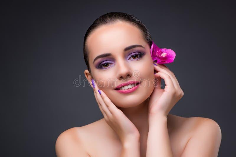 Młoda piękna kobieta z storczykowym kwiatem zdjęcia stock