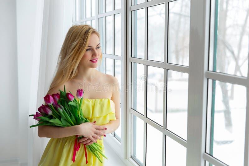 Młoda piękna kobieta z tulipanową wiązką w kolor żółty sukni przy okno zdjęcia stock