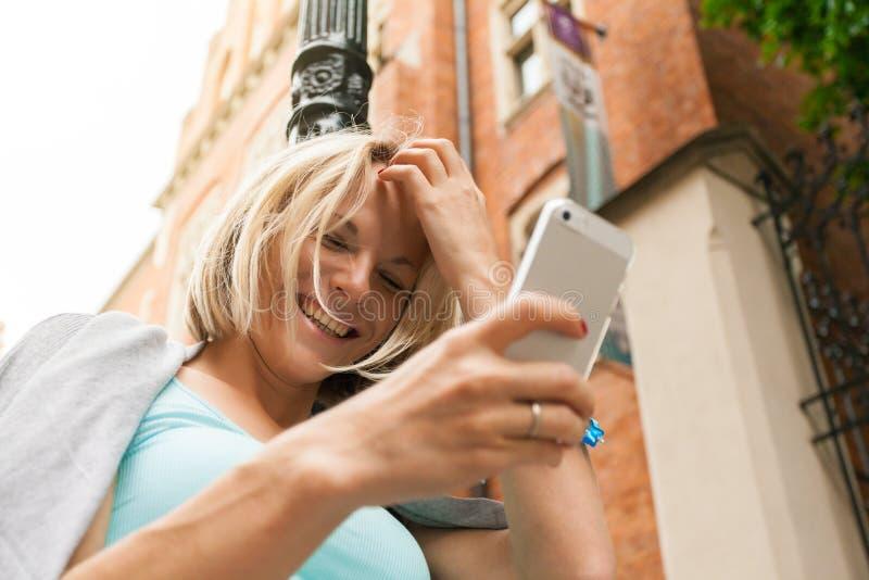 Młoda piękna kobiety pozycja z telefonem komórkowym przeciw tłu stary ceglany dom zdjęcie royalty free