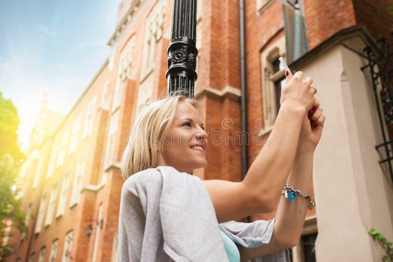 Młoda piękna kobiety pozycja z telefonem komórkowym przeciw tłu stary ceglany dom zdjęcia stock