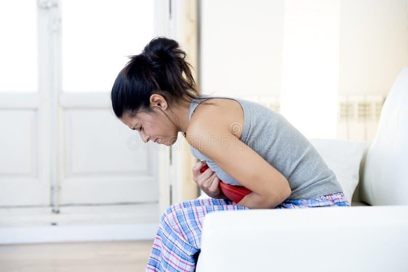 Młoda piękna latynoska kobiety mienia gorącej wody butelka przeciw brzuchowi cierpi menstrual okresu ból obraz stock
