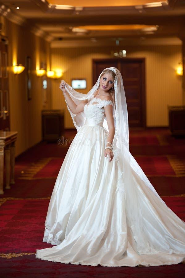 Młoda piękna luksusowa kobieta w ślubnej sukni pozuje w luksusowym wnętrzu Wspaniała elegancka panna młoda z długą przesłoną Pełn zdjęcia royalty free