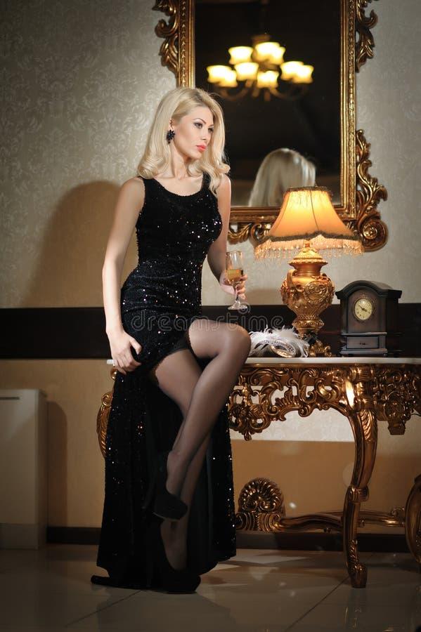 Młoda piękna luksusowa kobieta w długiej eleganckiej czerni sukni. Piękna młoda blondynki kobieta z jaskrawymi światłami w tle obraz stock
