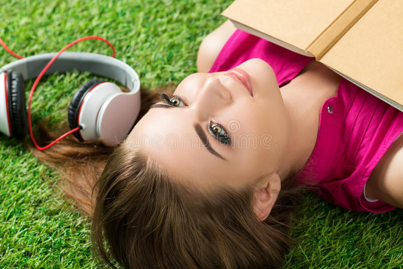 Młoda piękna marzycielska kobieta kłaść na trawie w parku zdjęcia stock
