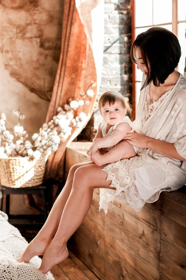 Młoda piękna matka trzyma jej małej córki siedzi na drewnianym nadokiennym parapecie zdjęcie stock