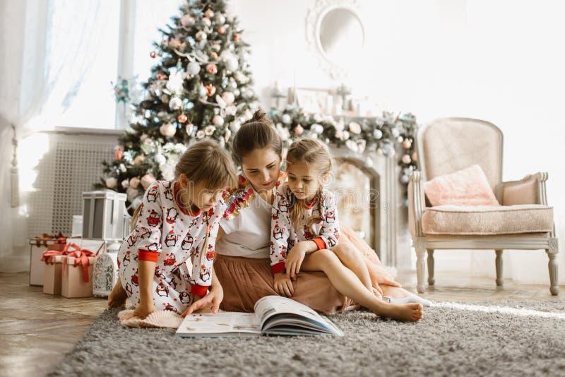 Młoda piękna matka z dwa małymi córkami siedzi na dywanie i czyta książkę blisko nowego roku drzewa z prezentami wewnątrz obrazy royalty free