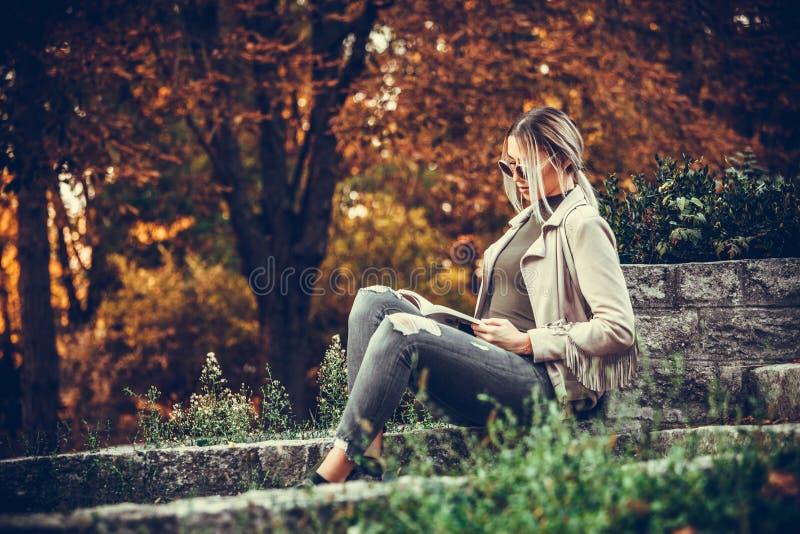 Młoda piękna miastowa kobieta jest czytelniczym książką podczas gdy siedzący w zdjęcia royalty free