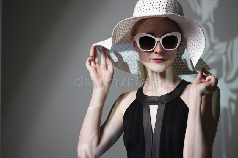Młoda piękna modna kobieta z modnym makeup Model patrzeje kamerę, jest ubranym eleganckich eyeglasses, kapelusz Żeńska moda, był obraz stock