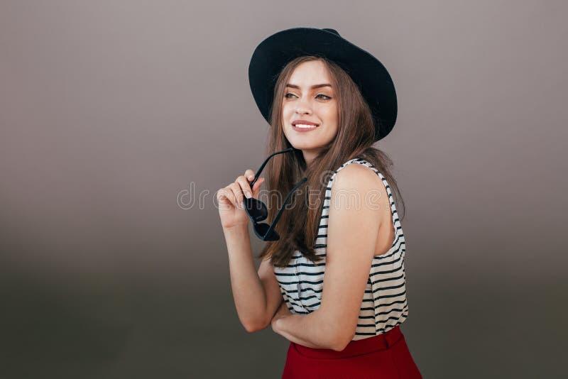 Młoda piękna modna kobieta z modnym makeup w czarnym kapeluszu i szkłach na popielatym tle Model patrzeje kamerę, w zdjęcia stock