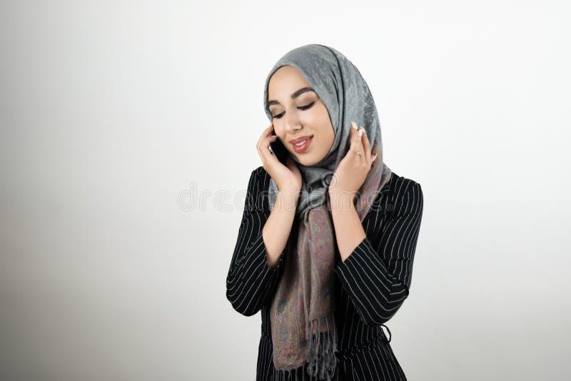 Młoda piękna Muzułmańska kobieta jest ubranym turbanu hijab chustkę na głowę opowiada na smartphone odizolowywał białego tło fotografia royalty free