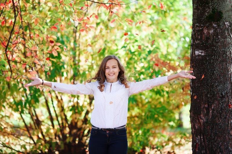 Młoda piękna nastolatek dziewczyna podrzuca kolorowych jesień liście w parku obrazy stock