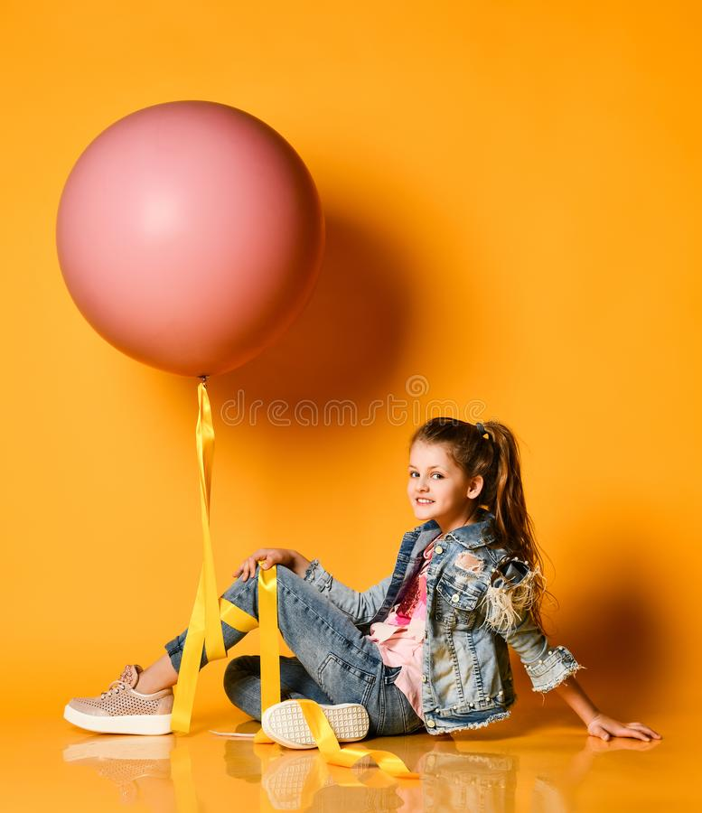 Młoda piękna nastolatek dziewczyna pozuje na żółtym tle, kłamstwa i podtrzymuje ogromnego gigant menchii balon Lato styl fotografia stock