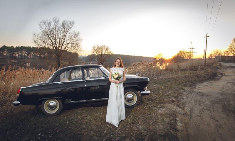 Młoda piękna panna młoda jest następnie blisko czernić retro samochodowego zmierzchu tło Poślubiać z rocznika starym retro samoch zdjęcie stock