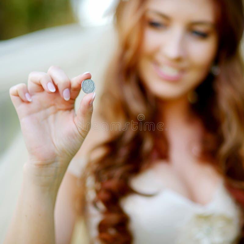 Młoda piękna panna młoda trzyma szczęsliwą monetę zdjęcie royalty free